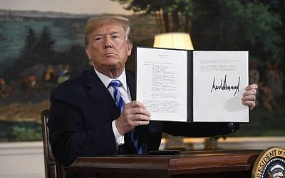 US President Donald Trump signs a document reinstating sanctions against Iran after announcing the US withdrawal from the Iran nuclear deal, in the Diplomatic Reception Room at the White House in Washington, DC, on May 8, 2018. (AFP PHOTO / SAUL LOEB)