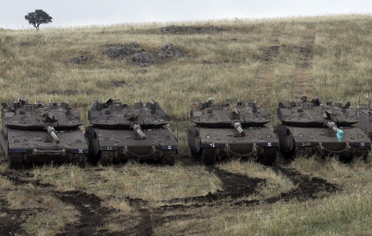 Israeli Merkava Mark IV tanks take positions near the Syrian border in the Golan Heights