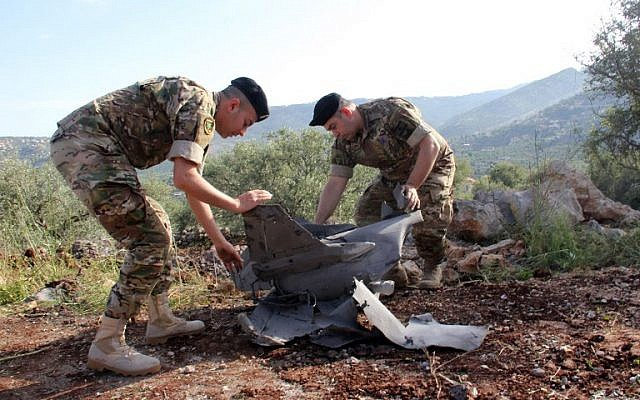 Lebanese soldiers inspect remains of a Syrian surface-to-air missile that had apparently been fired at Israeli jets during an extensive air campaign against Iranian targets in Syria, which landed in the southern Lebanese village of Hebarieh, on May 10, 2018. (Ali Dia/AFP)