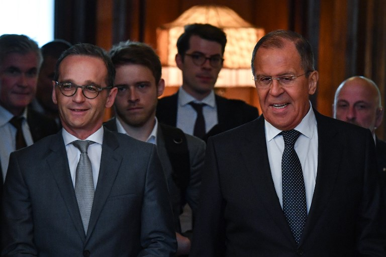 Russian Foreign Minister Sergei Lavrov and his German counterpart Heiko Maas enter a hall during a meeting in Moscow