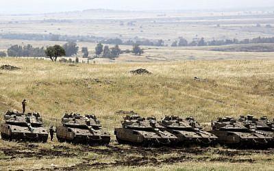 Israeli Merkava Mark IV tanks take positions near the Syrian border in the Golan Heights on May 10, 2018. (Menahem Kahana/AFP)