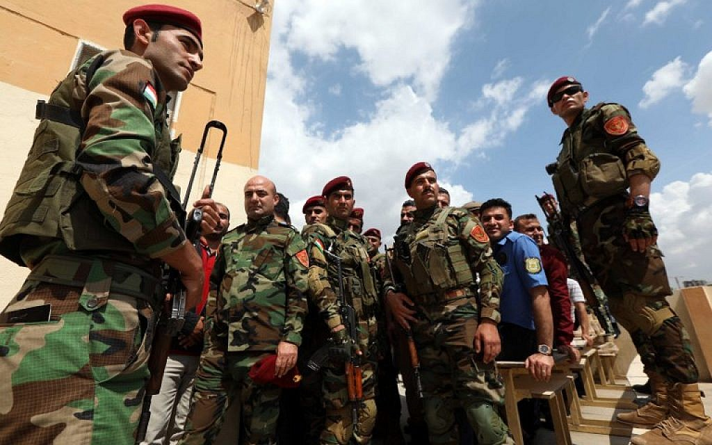 Iraqi Kurdish security members line up in front of a polling station to vote ahead of parliamentary elections in Arbil, the capital of the Kurdish autonomous region in northern Iraq on May 10, 2018. (AFP Photo/Safin Hamed)