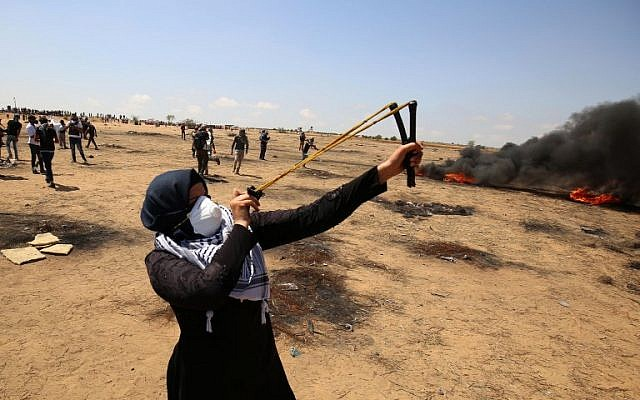 A demonstrator uses a slingshot to hurl stones during clashes with Israeli forces along the border with the Gaza strip east of Khan Younis on May 11, 2018. (AFP Photo/Said Khatib)
