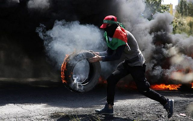 File: A Palestinian protester carries a burning tire during clashes between Palestinians and Israeli soldiers near Ramallah in the West Bank on, May 11, 2018. (AFP/Abbas Momani)