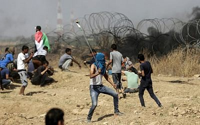 A Palestinian uses a slingshot to hurl stones during clashes with Israeli troops along the border between the Gaza Strip and Israel, east of Gaza City, on May 11, 2018. (AFP Photo/Mahmud Hams)