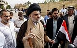 Iraqi Shiite cleric and leader Muqtada al-Sadr, center-left, shows his ink-stained index finger and holds a national flag while surrounded by people outside a polling station in the central holy city of Najaf on May 12, 2018. (Haidar Hamdani/AFP)