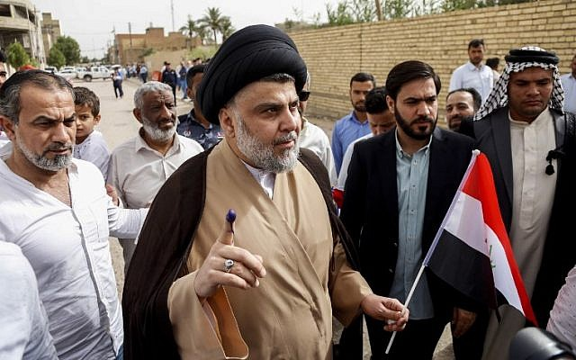Iraqi Shiite cleric and leader Moqtada al-Sadr, center-left, shows his ink-stained index finger and holds a national flag while surrounded by people outside a polling station in the central holy city of Najaf on May 12, 2018. (Haidar Hamdani/AFP)