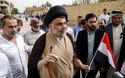 Iraqi Shiite leader Moqtada al-Sadr (C-L) shows his ink-stained index finger and holds an Iraqi flag outside a polling station in the holy city of Najaf on May 12, 2018, as the country votes in the first parliamentary election since declaring victory over the Islamic State terror group. (AFP Photo/Haidar Hamdani)