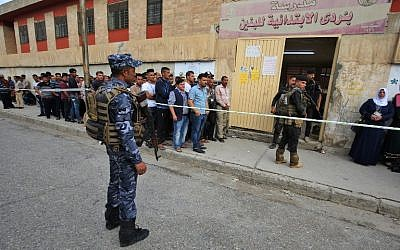 Members of the Iraqi security forces stand guard as people line up in front of a polling station in the Wadi Hajar district of Mosul on May 12, 2018. (AFP Photo/Ahmad al-Rubaye)