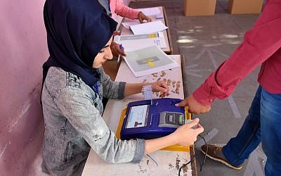 An Iraqi voter has his biometric voting card checked with his fingerprint upon arriving at a poll station in the northern multi-ethnic city of Kirkuk on May 12, 2018, as the country votes in the first parliamentary election since declaring victory over the Islamic State (IS) group. (AFP PHOTO / Marwan IBRAHIM)