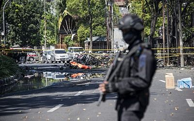 An Indonesian anti-terror policeman stands guard at the site of a suicide bomb attack outside a church in Surabaya on May 13, 2018. (AFP Photo/Juni Kriswanto)
