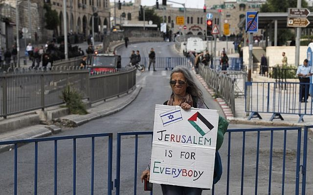 A woman holds a banner at Damascus gate ahead of the Jerusalem Day celebrations marking the unification of the city during the Six Day War, May 13, 2018. (Ahmad GHARABLI/AFP)