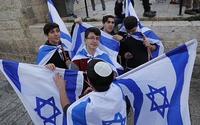 Israeli youths hold their national flag during a march to celebrate Jerusalem Day, marking the unification of the city during the Six Day War, May 13, 2018.  (Thomas COEX/AFP)