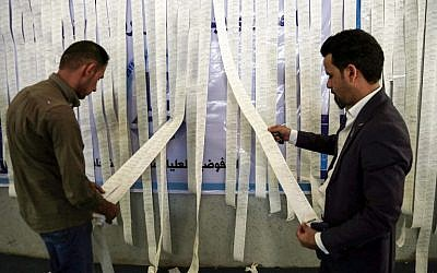 Iraqi electoral commission employees examine electronic counting machine print-outs in the holy city of Najaf on May 13, 2018, for the special round of voting that took place for the police and military on May 10 in the country's first parliamentary election since declaring victory over the Islamic State terror group. (AFP Photo/Haidar Hamdani)