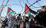 A girl raises a Palestinian flag as another Palestinian boy holds a wooden key symbolizing the return, as they stand with others before the barbed-wire marking the border between the Gaza strip and Israel east of Gaza City on May 13, 2018. (AFP/Mahmud Hams)