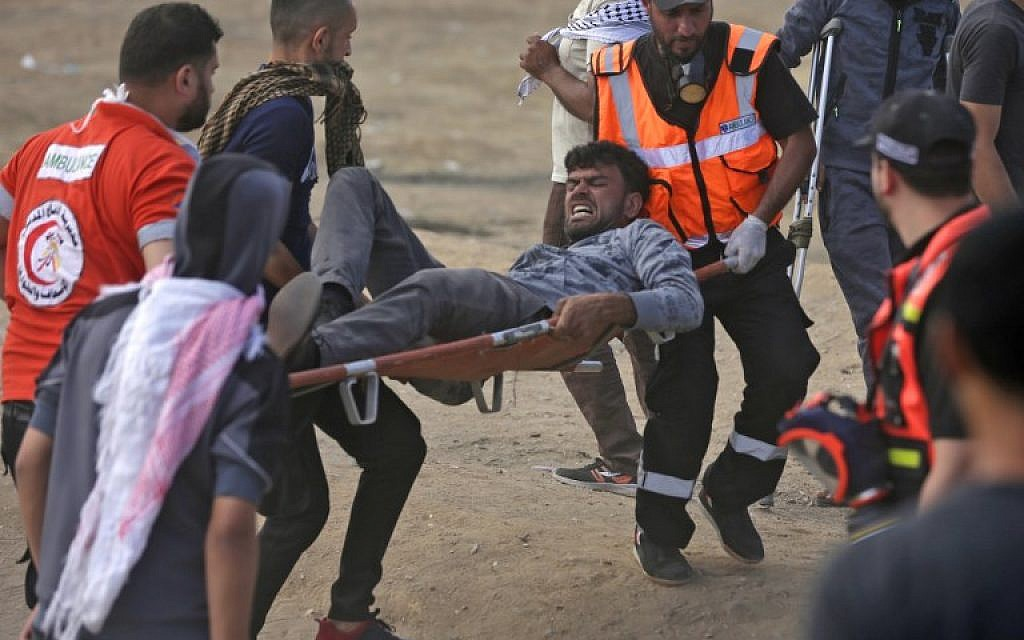 Palestinians carry a protester injured during clashes along the Gaza-Israel border, May 14, 2018 (AFP Photo/Mahmud Hams)
