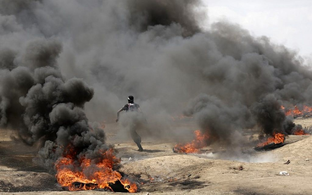 Palestinian demonstrators burn tires near the Gaza-Israel border, east of Gaza City, during protests over the inauguration of the US embassy in Jerusalem, May 14, 2018 (AFP Photo/Mahmud Hams)