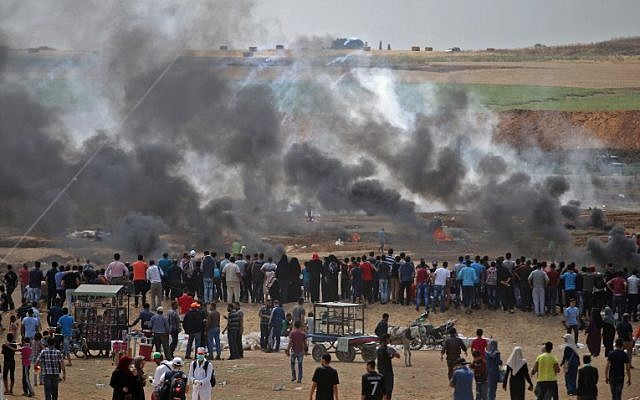 Palestinian protesters look at tear gas and smoke billowing from burning tires, east of Gaza City on May 14, 2018 (AFP PHOTO / Mohammed ABED)