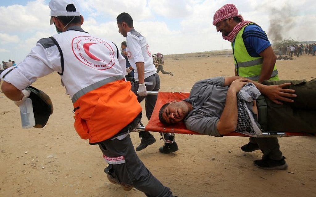 Palestinians carry a protester injured during clashes along the Gaza-Israel border, east of Khan Yunis,  May 14, 2018. (AFP Photo/Said Kahtib)