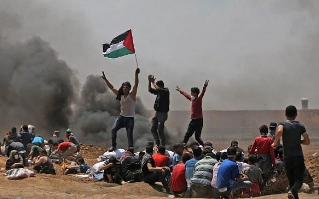 Palestinians wave their national flag as they demonstrate near the border between Israel and the Gaza Strip, east of Jabaliya, on May 14, 2018. (AFP PHOTO / MOHAMMED ABED)