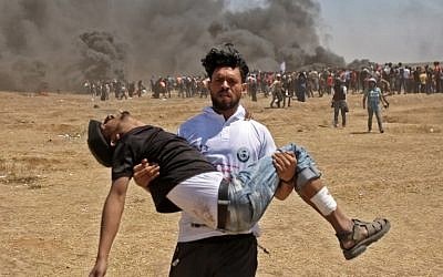 A Palestinian carries an injured protester during clashes with Israeli forces near the border between the Gaza strip and Israel east of Gaza City on May 14, 2018. (AFP / MAHMUD HAMS)