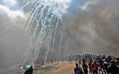 Palestinians run for cover from tear gas fired by Israeli forces near the border between the Gaza strip and Israel east of Gaza City on May 14, 2018. (AFP/ MAHMUD HAMS)
