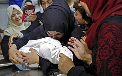 The mother of a Leila Ghandour, a Palestinian baby of 8 months who according to Gaza's health ministry died of tear gas inhalation during clashes in East Gaza on May 14, 2018, holds her at the morgue of al-Shifa hospital in Gaza City on May 15, 2018. On May 16, the ministry said the cause of death had not been definitively established. (AFP/Thomas Coex)