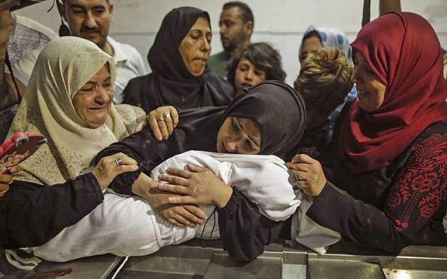 The mother of Layla Ghandour holds her at the morgue of al-Shifa hospital in Gaza City on May 15, 2018. (AFP / MAHMUD HAMS)