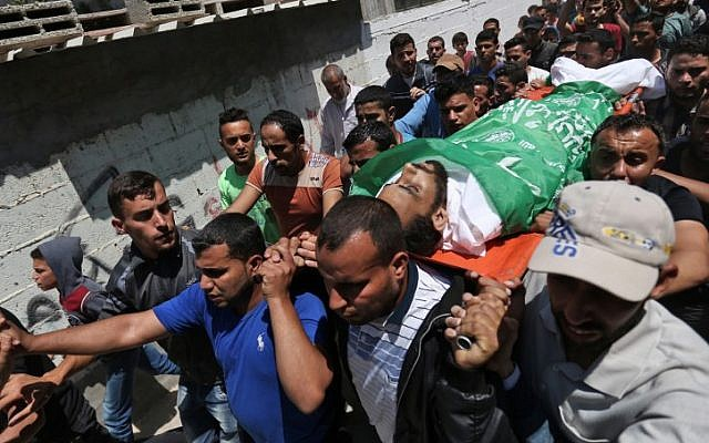 Mourners carry the body of Mohammed Dwedar a 27 year-old Palestinian killed during clashes along the Gaza border the previous day, during his funeral in Nusseirat refugee camp in the Gaza Strip on May 15, 2018. (AFP PHOTO / MOHAMMED ABED)