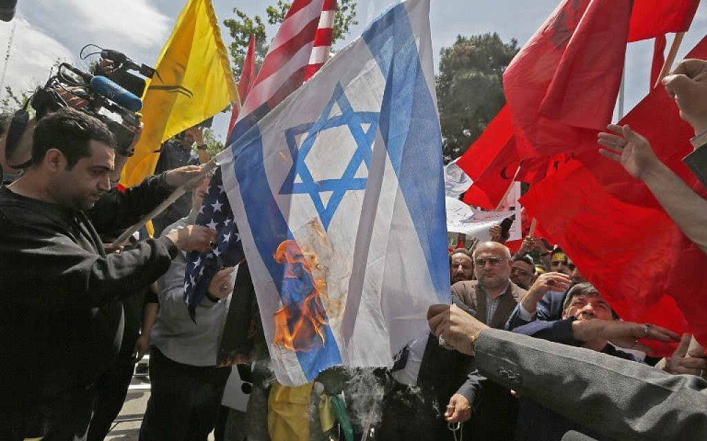 Iranians burn US and Israeli flags during a demonstration inside the former US embassy headquarters in the capital Tehran on May 16, 2018. (AFP/ ATTA KENARE)