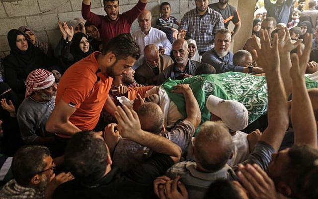 Palestinian mourners carry the body of 51-year-old Nasser Ghorab during his funeral in al-Nusirat refugee camp in the central Gaza Strip on May 16, 2018. (AFP/MAHMUD HAMS)