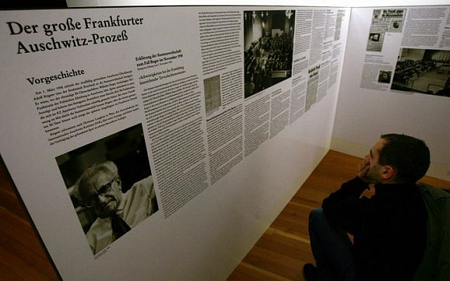 In this photo taken on November 14, 2004, a visitor reads about the 'Frankfurt Trial' of Auschwitz's Nazi commanders, initiated by German-Jewish Magistrate Fritz Bauer (L), at an exhibition at the Martin Gropius Museum in Berlin. (AFP/John MacDougall)