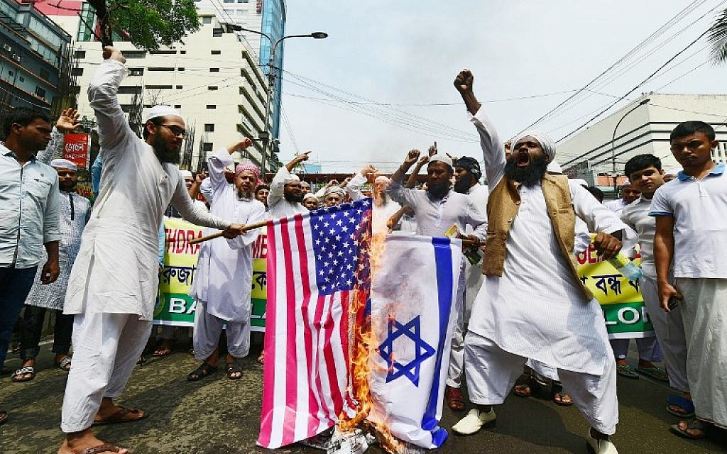 Activists from an Islamic organization burn the US and Israel flags during a protest after prayers on the first Friday of the holy month of Ramadan at a mosque in Dhaka on May 18, 2018. (AFP Photo/Munir Uz Zaman)