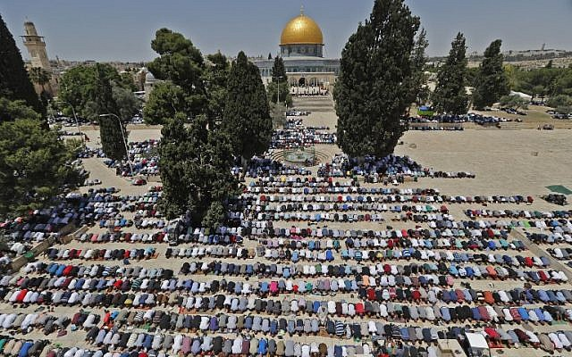 Muslim worshippers pray near the Dome of the Rock and the Al-Aqsa Mosque, located on the Temple Mount compound in Jerusalem, during the first Friday prayers of the holy month of Ramadan on May 18, 2018 (AFP Photo/Ahmad Gharabli)