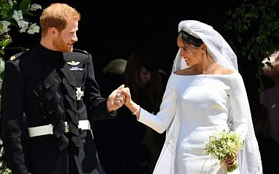 Britain's Prince Harry, Duke of Sussex and his wife Meghan, Duchess of Sussex leave from the West Door of St George's Chapel, Windsor Castle, in Windsor, on May 19, 2018 after their wedding ceremony. (AFP/ Ben Birchall)