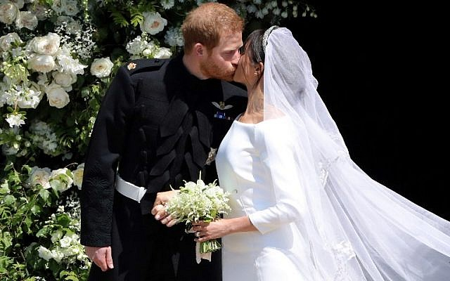 Britain's Prince Harry, Duke of Sussex kisses his wife Meghan, Duchess of Sussex as they leave from the West Door of St George's Chapel, Windsor Castle, in Windsor, on May 19, 2018 after their wedding ceremony. (AFP/ Andrew Matthews)