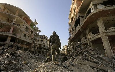 Syrian government forces walk down a destroyed street at the entrance of the Palestinian camp of Yarmouk on the southern outskirts of Damascus on May 21, 2018, after the Syrian army announced it was in complete control of the capital and its outskirts for the first time since 2012, following the ousting of the Islamic State group (AFP PHOTO / LOUAI BESHARA)