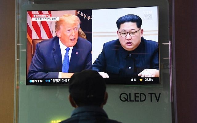 A man watches a television news screen showing US President Donald Trump, left, and North Korean leader Kim Jong Un, at a railway station in Seoul on May 25, 2018. (AFP/Jung Yeon-je)