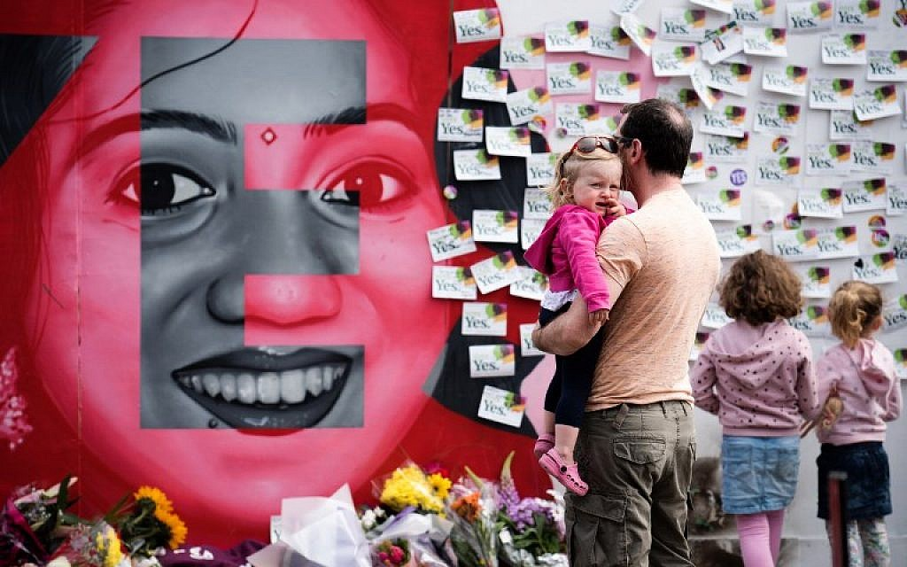"""Floral tributes are laid at a mural to Savita Halappanavar, a 31-year-old Indian dentist, who died in 2012 due to the complications of a septic miscarriage at 17 weeks' gestation, in Camden Street, Dublin, Ireland on May 26, 2018, during the Irish referendum on liberalizing the abortion law. Ireland looks set to """"make history"""" by liberalizing some of the strictest abortion laws in Europe, Prime Minister Leo Varadkar said as votes in the hard-fought referendum were counted on May 26, 2018. (AFP PHOTO / BARRY CRONIN)"""
