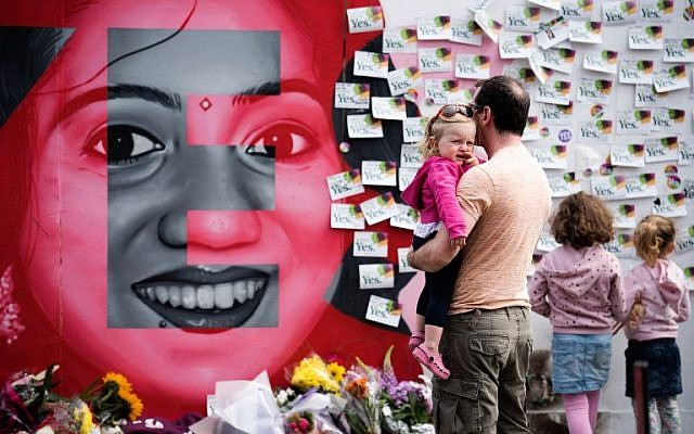 "Floral tributes are laid at a mural to Savita Halappanavar, a 31-year-old Indian dentist, who died in 2012 due to the complications of a septic miscarriage at 17 weeks' gestation, in Camden Street, Dublin, Ireland on May 26, 2018, during the Irish referendum on liberalizing the abortion law. Ireland looks set to ""make history"" by liberalizing some of the strictest abortion laws in Europe, Prime Minister Leo Varadkar said as votes in the hard-fought referendum were counted on May 26, 2018. (AFP PHOTO / BARRY CRONIN)"