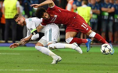Liverpool's Egyptian forward Mohamed Salah (R) falls with Real Madrid's Spanish defender Sergio Ramos leading to Salah being injured during the UEFA Champions League final football match between Liverpool and Real Madrid at the Olympic Stadium in Kiev, Ukraine, on May 26, 2018. (AFP PHOTO/GENYA SAVILOV)