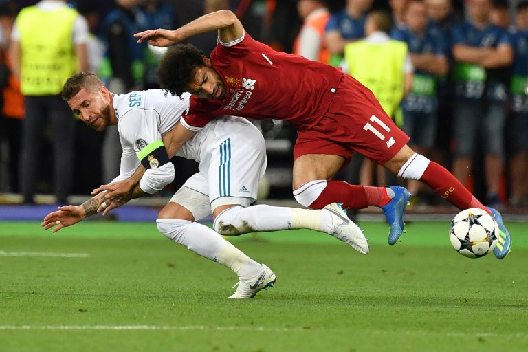 e87c41e17 Liverpool s Egyptian forward Mohamed Salah (R) falls with Real Madrid s  Spanish defender Sergio Ramos