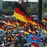 """Alternative for Germany (AfD)'s demonstrators holding placards and German flags gather at the main station in Berlin to attend the """"demonstration for the future of Germany"""" called by the far-right AfD in Berlin on May 27, 2018. (AFP PHOTO / Odd ANDERSEN)"""