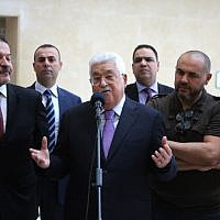 Palestinian Authority President Mahmoud Abbas, flanked by his two sons Yasser, left, and Tarek, right, gives a short statement before leaving a Ramallah hospital on May 28, 2018. (AFP Photo/Abbas Momani)