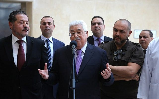 Palestinian Authority President Mahmoud Abbas, flanked by his two sons Yasser (L) and Tarek (R), gives a short statement before leaving a hospital near Ramallah in the West Bank on May 28, 2018. (AFP PHOTO / ABBAS MOMANI)