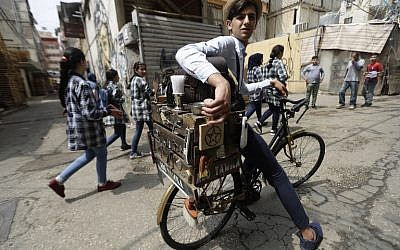 """Mohammed, a Lebanese roaming barber, better known as """"Abo Tawila,"""" rides his bicycle on the outskirts of the Palestinian refugee camp of Burj al-Barjaneh, south of the capital Beirut on May 29, 2018. (AFP PHOTO / JOSEPH EID)"""