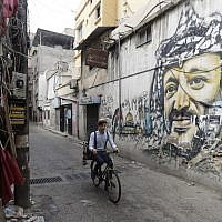 Mohammed, a Lebanese roaming barber, better known as 'Abo Tawila,' rides his bicycle in a street on the outskirts of the Palestinian refugee camp Burj al-Barajneh, south of the capital Beirut on May 29, 2018. (AFP PHOTO / JOSEPH EID)