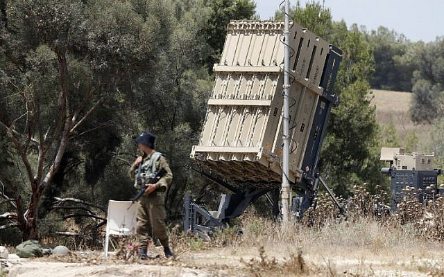 Israeli soldiers stand guard next to an Iron Dome defense system, designed to intercept and destroy incoming short-range rockets and artillery shells, deployed along the border with the Gaza Strip on May 29, 2018. (AFP Photo/Jack Guez)