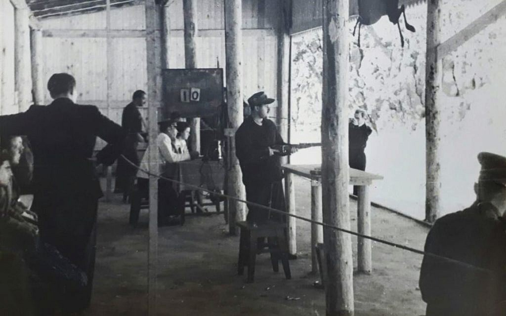 Joseph Schneider holds a rifle in a shooting course. (Courtesy National Library of Israel)