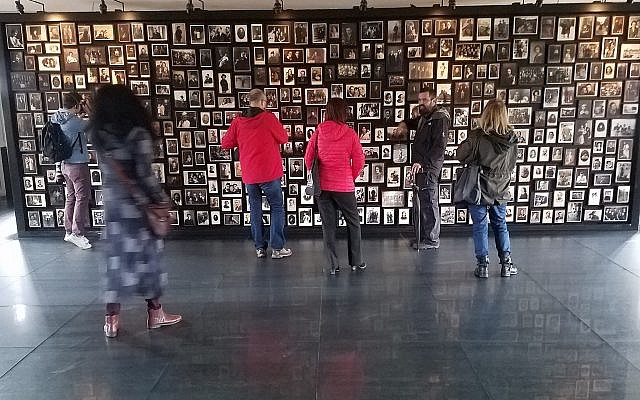 A Holocaust memorial created in the 'sauna' facility of the former German Nazi death camp Auschwitz-Birkenau, in Poland, with photographs of people deported there, October 2017 (Matt Lebovic/The Times of Israel)